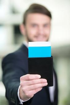Empresário com uma mala e bilhetes de avião no aeroporto