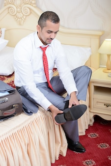 Empresário com uma mala, sentado na cama.