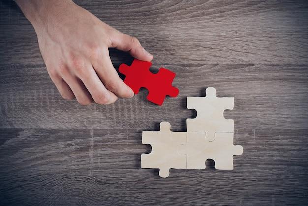 Empresário completa um quebra-cabeça inserindo uma peça que faltava