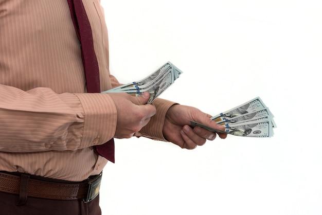 Empresário comprando ou alugando um produto ou serviço, dando dólares, isolados no branco. a mão masculina oferece um suborno