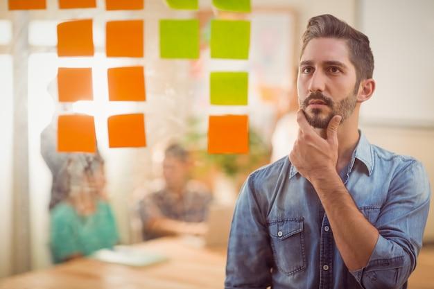 Empresário concentrado que olha o poste na parede