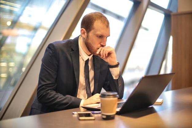 Empresário, concentrando-se em algo que ele está lendo em seu laptop Foto Premium