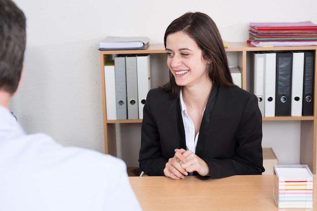 Empresário, conduzindo uma entrevista de emprego, sentado em sua mesa em seu escritório na frente de potencial candidato do sexo feminino