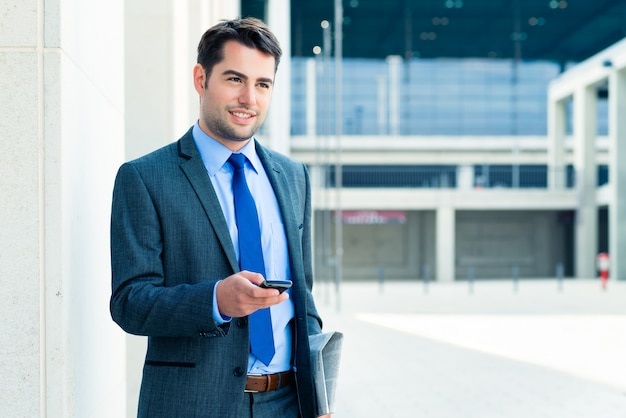 Empresário confiante ao ar livre usando telefone