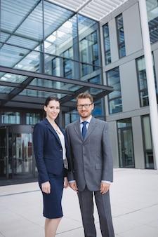 Empresário confiante com um colega do lado de fora do prédio
