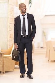Empresário confiante. comprimento total de um jovem africano alegre em trajes formais, segurando uma pasta e sorrindo