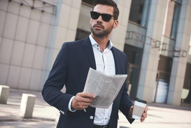 Empresário confiante e feliz jovem empresário lendo jornal do lado de fora do prédio de escritórios