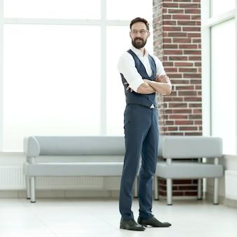 Empresário confiante em pé no saguão do escritório.