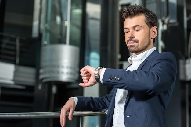 Empresário confiante está olhando para o relógio.