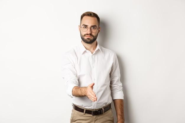 Empresário confiante estende a mão para um aperto de mão, cumprimentando o parceiro de negócios, em pé sobre um fundo branco