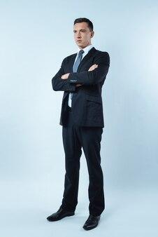 Empresário confiante. homem bonito sério e simpático de pé contra um fundo azul e cruzando os braços enquanto mostra sua confiança