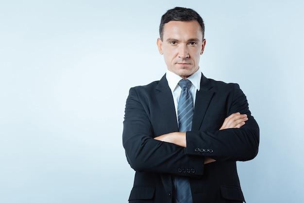 Empresário confiante. homem sério, simpático, bonito, de pé, armado e olhando para você enquanto mostra confiança