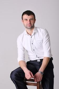 Empresário confiante. jovem bonito na camisa em pé na parede branca.