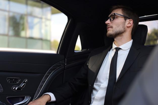 Empresário confiante pensativo em um terno completo com óculos, olhando para longe enquanto está sentado no carro.