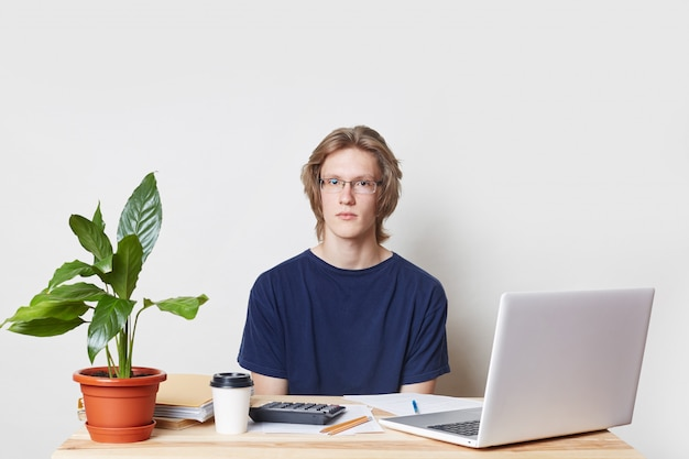 Empresário confiante prepara relatório anual, figuras de calcualtes, usa computador portátil moderno e calculadora, bebe café para viagem, olha seriamente para a câmera, isolada sobre a parede branca