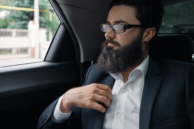 Empresário confiante, sentado no carro volta sente-se
