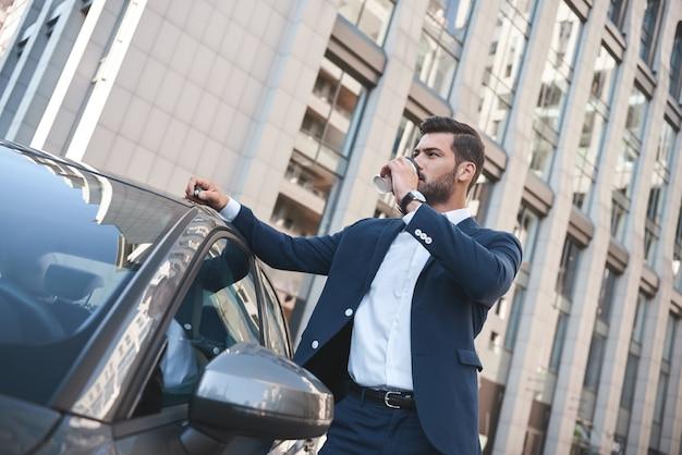 Empresário confiante tomando café para ir enquanto está perto de um carro na rua
