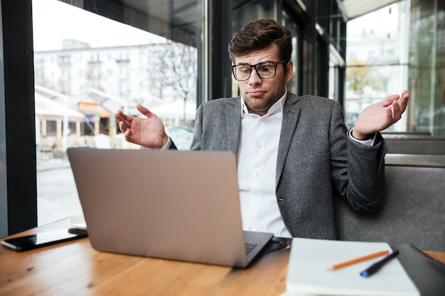 Empresário confuso em óculos, sentado junto à mesa no café enquanto encolhe os ombros e olhando para o computador portátil