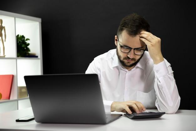 Empresário confuso olha tristemente para calculadora e resolve problemas financeiros