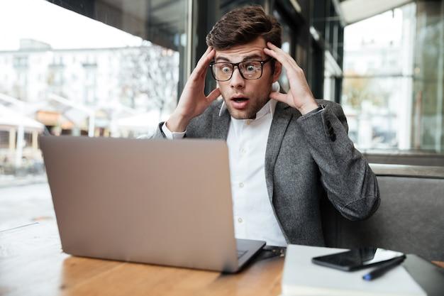 Empresário confuso preocupado em óculos, sentado junto à mesa no café, mantendo a cabeça e olhando para o computador portátil