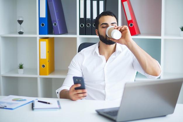 Empresário considerável novo que senta-se na mesa e que usa o portátil no escritório.