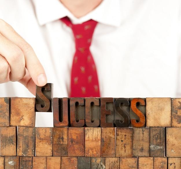 Empresário, construindo a palavra sucesso em tipografia na parede branca