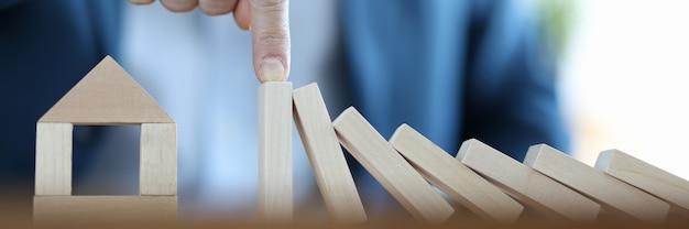 Empresário construiu casa de blocos de madeira. conceito de seguro de acidentes imobiliários
