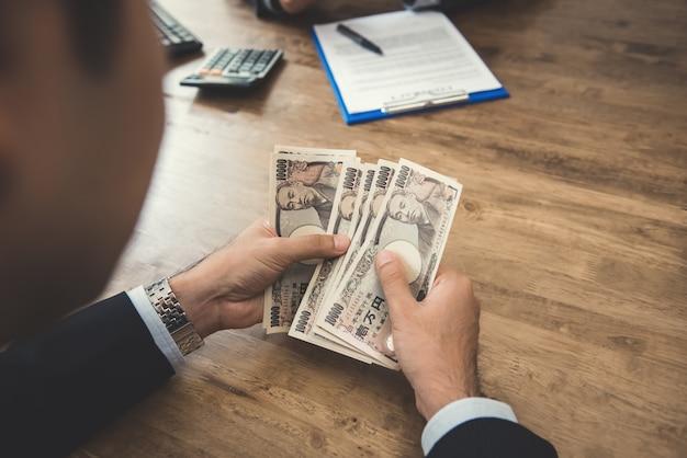 Empresário contando dinheiro, notas de ienes japoneses, ao fazer um acordo