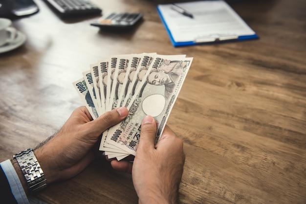 Empresário contando dinheiro notas de ienes japoneses