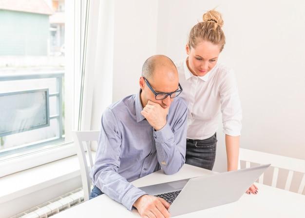 Empresário contemplativo e empresária olhando para laptop