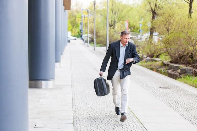 Empresário correndo na cidade e olhando para o relógio