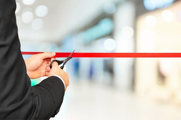 Empresário cortando fita vermelha com tesoura