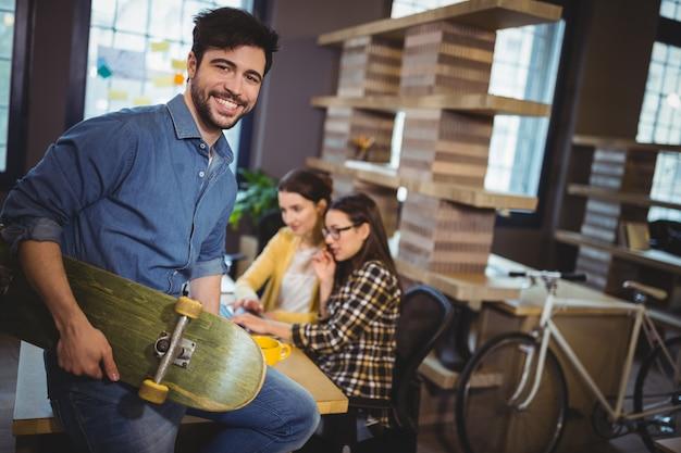 Empresário criativo segurando o skate enquanto está sentado na mesa