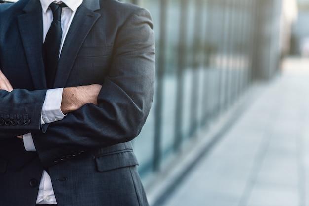 Empresário, cruzando as mãos, posando no fundo do prédio de escritórios