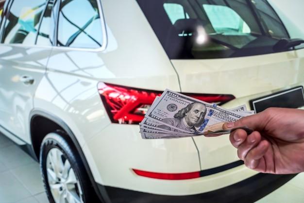 Empresário dá dinheiro para alugar um carro nas férias de verão. conceito de finanças