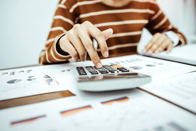 Empresário da jovem mulher que trabalha com papel e usando a calculadora para calcular as despesas domésticas financeiras na sala de estar na mesa.