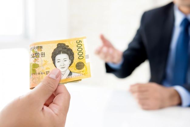 Empresário dando dinheiro ao seu parceiro em forma de won sul-coreano