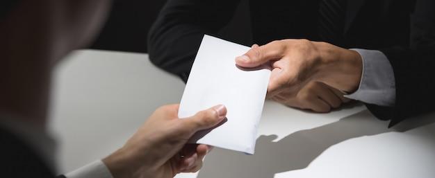 Empresário dando dinheiro de suborno no envelope para parceiro