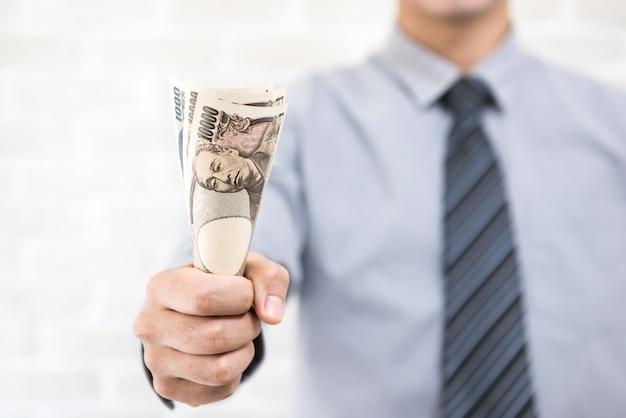 Empresário dando dinheiro iene japonês