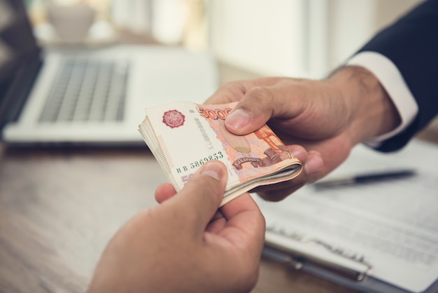 Empresário dando dinheiro, moeda rublo russo, para seu parceiro