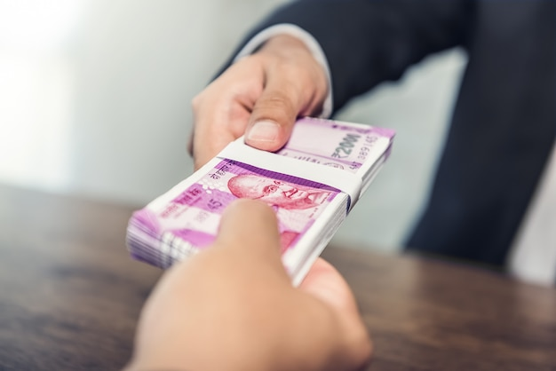 Empresário dando dinheiro, moeda rupia indiana, ao seu parceiro
