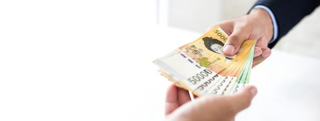 Empresário dando dinheiro won sul-coreano moeda para seu fundo de banner de parceiro