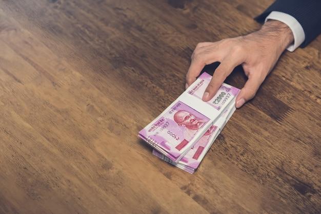 Empresário dando (oferecendo) pilha de dinheiro, moeda rupia indiana, em cima da mesa