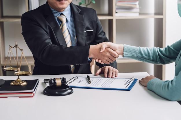 Empresário de advogado apertando as mãos de clientes faz um contrato para trabalhar o macete colocado na mesa do escritório.