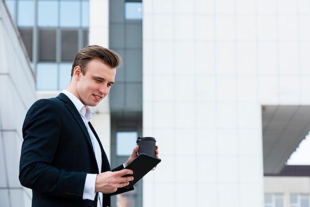 Empresário de baixo ângulo usando tablet