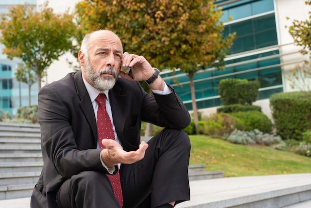 Empresário de cabelos cinza irritado, falando no telefone