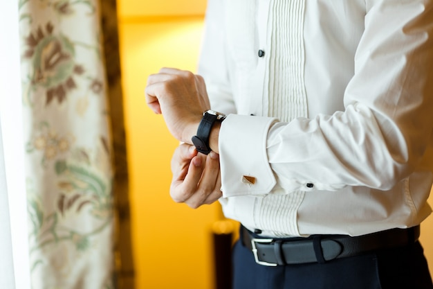 Empresário de camisa branca, cinto de couro preto e abotoaduras usando seu relógio caro