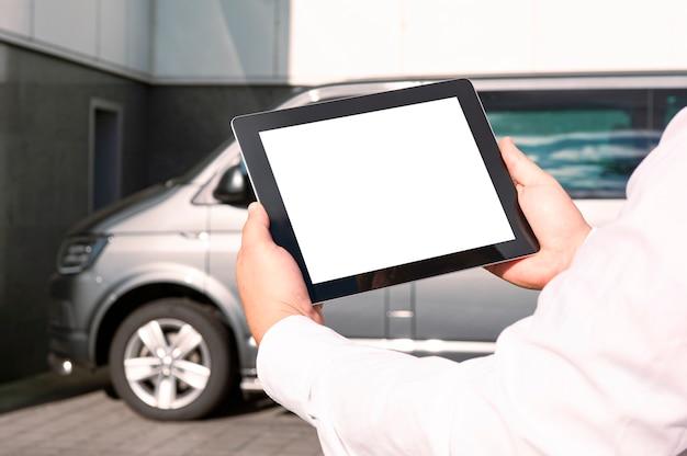 Empresário de camisa branca segurando um tablet