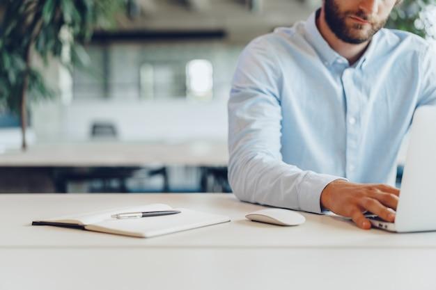 Empresário de camisa trabalhando em seu laptop em um escritório. escritório em espaço aberto