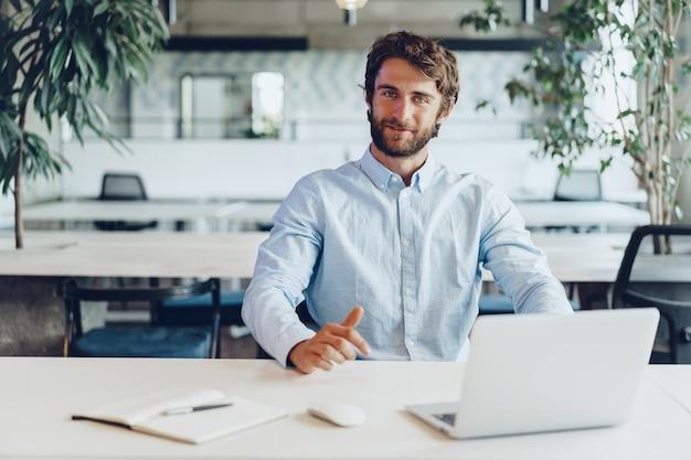 Empresário de camisa trabalhando em seu laptop em um escritório.